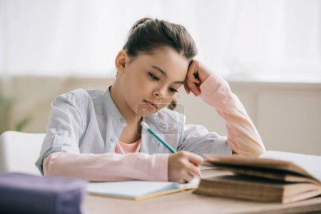 Foto de Thoughtful schoolchild writing in notebook while sitting at desk and doing homework - Imagen libre de derechos