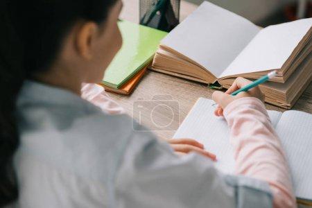 Photo pour Vue arrière de l'élève écrivant dans un cahier tout en étant assis au bureau et faisant ses devoirs - image libre de droit