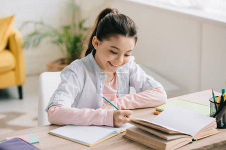 Foto de Adorable niño alegre escribiendo en la libreta mientras se sienta en el escritorio cerca del libro y haciendo la tarea de la escuela en casa - Imagen libre de derechos