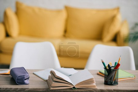 Photo for Selective focus of wooden desk with open book, copy books, pencil case and stationery - Royalty Free Image