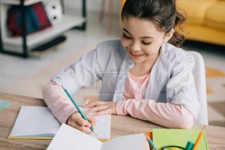 Foto de Vista de ángulo alto de adorable niño haciendo la tarea y escribir en cuaderno - Imagen libre de derechos