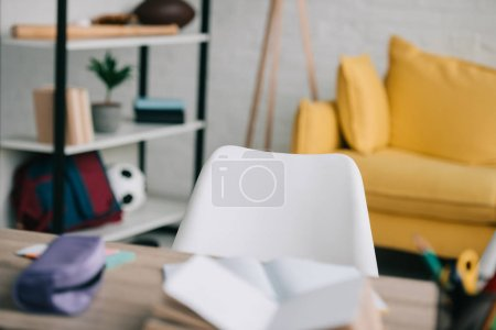 Photo pour Foyer sélectif de bureau avec des livres de copie et de papeterie, étagère et canapé jaune - image libre de droit