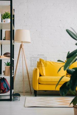Photo pour Salon léger avec canapé jaune, rack, tapis sur le sol et la lampe de sol - image libre de droit