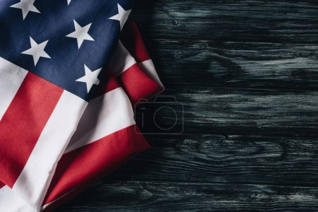 folded american national flags on grey wooden surface, memorial day concept