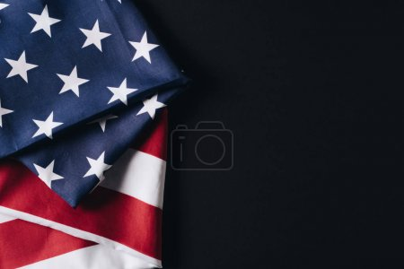 folded national flag of usa isolated on black, memorial day concept