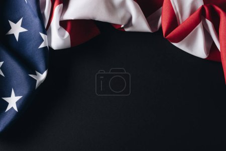 folded united states of america national flag isolated on black, memorial day concept