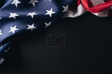 folded american national flag isolated on black, memorial day concept