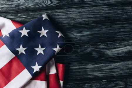 folded national flag of united states of america on wooden surface, memorial day concept