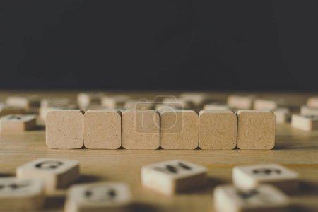 Photo pour Foyer sélectif de six cubes vierges entourés de blocs avec des lettres sur la surface en bois isolé sur noir - image libre de droit
