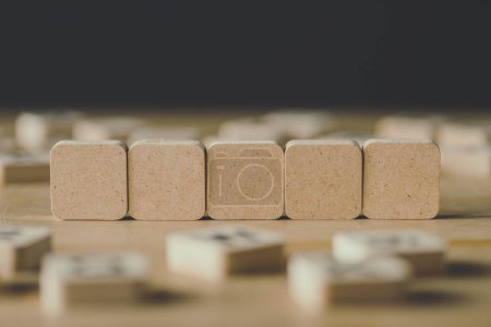 Photo for Selective focus of five blank cubes surrounded by blocks with letters on wooden surface isolated on black - Royalty Free Image