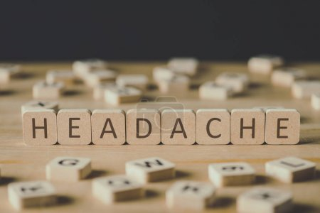 Photo for Selective focus of headache lettering on cubes surrounded by blocks with letters on wooden surface isolated on black - Royalty Free Image