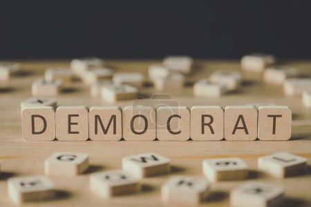 Photo for Selective focus of word democrat made of cubes surrounded by blocks with letters on wooden surface isolated on black - Royalty Free Image