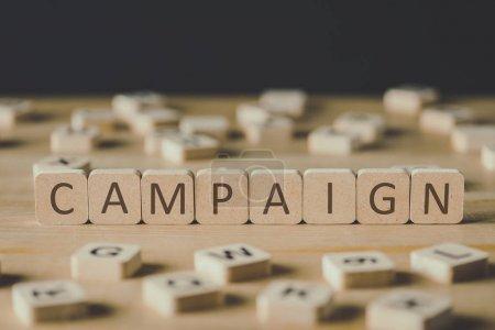 Photo pour Foyer sélectif de la campagne de mot faite de cubes entourés de blocs avec des lettres sur la surface en bois isolée sur le noir - image libre de droit