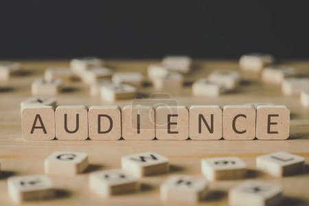 Foto de Selective focus of audience lettering on cubes surrounded by blocks with letters on wooden surface isolated on black - Imagen libre de derechos