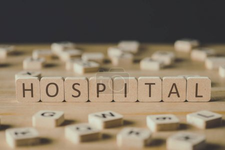Photo for Selective focus of cubes with word hospital surrounded by blocks with letters on wooden surface isolated on black - Royalty Free Image