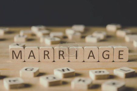 Photo for Selective focus of word marriage made of cubes surrounded by blocks with letters on wooden surface isolated on black - Royalty Free Image