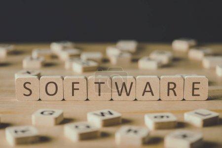 Photo pour Mise au point sélective du lettrage logiciel sur des cubes entourés de blocs avec des lettres sur la surface en bois isolée sur le noir - image libre de droit