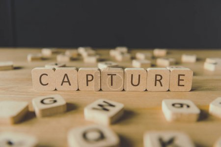 Photo pour Mise au point sélective de la capture de mot faite de cubes entourés de blocs avec des lettres sur la surface en bois isolée sur le noir - image libre de droit
