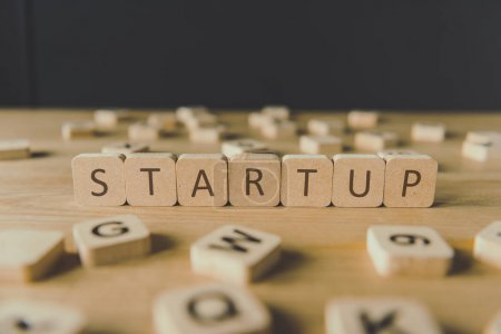 selective focus of startup inscription on cubes surrounded by blocks with letters on wooden surface isolated on black