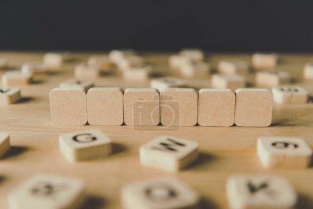 Photo pour Foyer sélectif de six cubes vides entourés de blocs avec des lettres sur la surface en bois isolé sur noir - image libre de droit