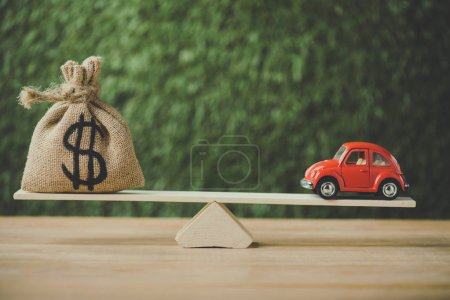 Photo for Toy car and money bag with dollar sign balancing on seesaw on green background - Royalty Free Image