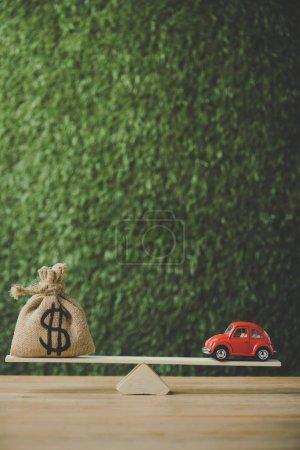 Photo pour Maison modèle et sac d'argent avec symbole dollar équilibrage sur balançoire sur fond vert - image libre de droit