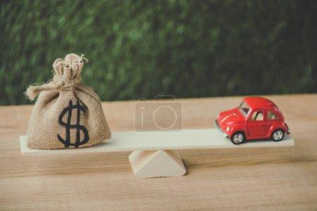 Photo pour Voiture miniature rouge et sac d'argent avec signe dollar équilibrage sur balançoire sur fond vert - image libre de droit