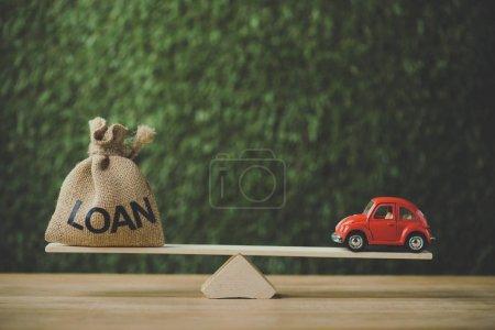 Photo pour Voiture miniature rouge et sac d'argent avec prêt mot équilibrage sur balançoire sur fond vert - image libre de droit