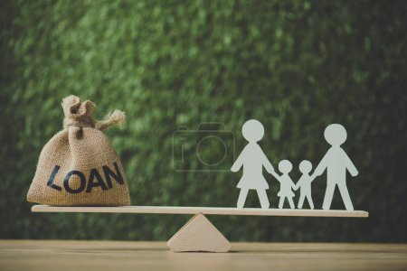 Photo pour Money bag with loan inscription and paper cut family balancing on see saw on green background - image libre de droit