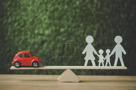 Photo pour Red miniature car and paper cut family balancing on swing on green background - image libre de droit