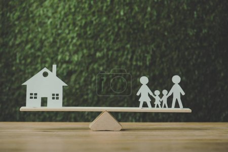 paper cut house and paper family balancing on seesaw on green background