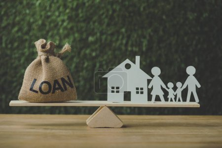 Photo pour Maison en papier et papier coupe famille équilibrage sur balançoire avec sac d'argent avec inscription de prêt sur fond vert - image libre de droit