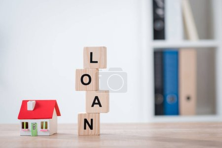 Photo for Word loan made of wooden cubes and house model on wooden tabletop surface - Royalty Free Image