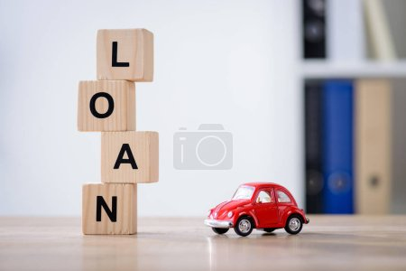 Photo pour Wooden cubes with loan lettering and red toy car on wooden tabletop surface - image libre de droit