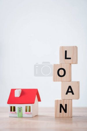Photo for House model and wooden cubes with word loan on wooden surface isolated on grey - Royalty Free Image