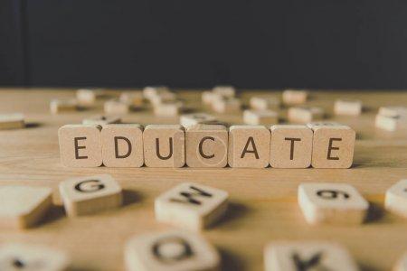 Photo pour Mise au point sélective de mot éduquer fait de cubes entourés de blocs avec des lettres sur la surface en bois isolé sur le noir - image libre de droit