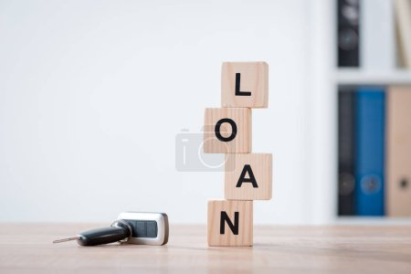 Photo for Car keys and wooden cubes with word loan on wooden tabletop surface in office - Royalty Free Image