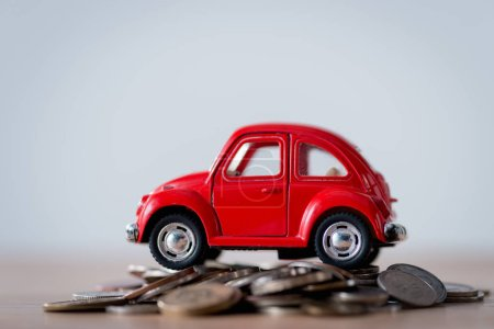 Photo pour Red toy car on metal coins on wooden surface isolated on grey - image libre de droit