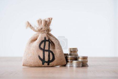 Photo pour Sac d'argent avec le signe de dollar et les piles des pièces en métal sur la surface en bois d'isolement sur le gris - image libre de droit