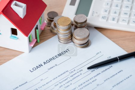 Photo pour Loan agreement, house model, calculator, silver and golden coins on wooden surface - image libre de droit