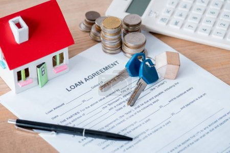 loan agreement, house model, keys, coins and calculator on wooden surface