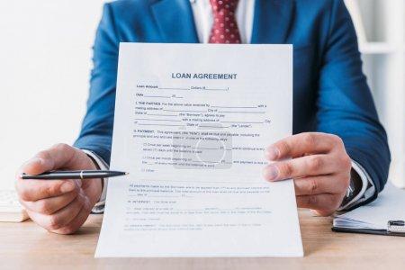 Photo pour Partial view of businessman pointing with pen at loan agreement - image libre de droit