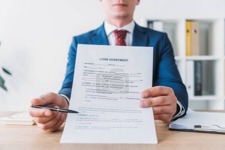 Photo pour Cropped view of manager pointing with pen at loan agreement - image libre de droit