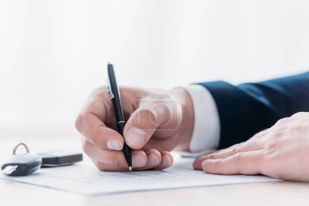 Photo pour Partial view of businessman holding pen and writing in loan agreement and car keys on tabletop - image libre de droit