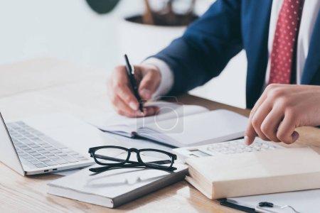 Photo pour Vue partielle de l'homme d'affaires en tenue formelle en utilisant une calculatrice et en écrivant dans un cahier sur le lieu de travail - image libre de droit