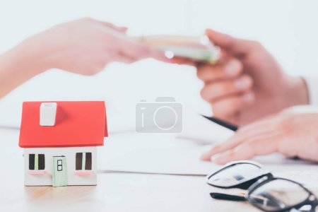 partial view of businessman taking money from client near house model on tabletop