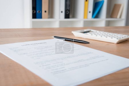 Photo for Loan agreement, pen and calculator on wooden table in office - Royalty Free Image