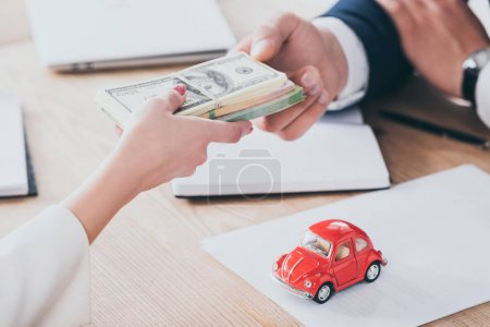Photo pour Cropped shot of client giving money to businessman near red toy car on tabletop - image libre de droit