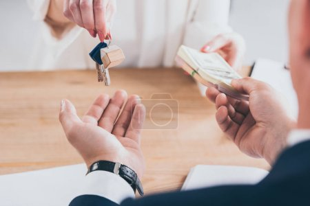 Photo pour Cropped shot of businessman taking money from customer holding keys - image libre de droit