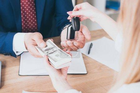Photo pour Vue recadrée de l'homme d'affaires prenant des billets de banque de dollar des clefs de voiture de fixation de client - image libre de droit